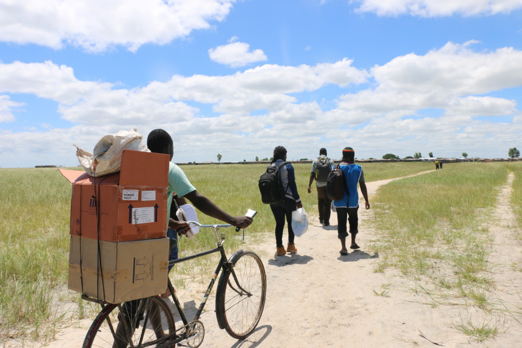A bicycle taxi operator helps carry supplies to the interior coastal areas of Lake Chirwa as the DI team walk in the scorching sun.